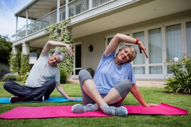 Couples aînés, exécuter, étirage, exercice, sur, tapis exercice