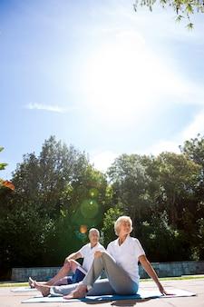 Couples aînés, exercisme, à, bord piscine, contre, ciel