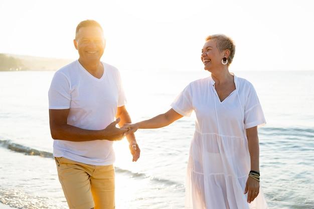 Couples aînés, tenant mains, à, bord mer