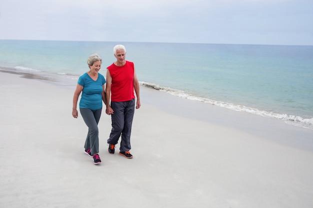 Couples aînés, tenant mains, et, marcher plage
