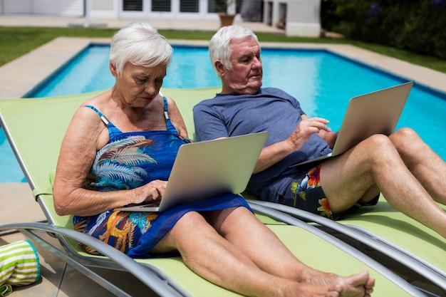 Couples aînés, utilisation, ordinateur portable, sur, chaise longue, à, piscine