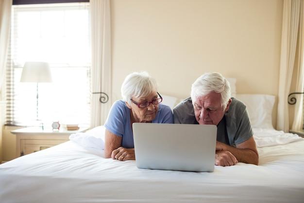 Couples aînés, utilisation, ordinateur portable, lit, dans, chambre à coucher, chez soi