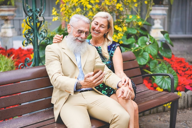 Couples aînés, utilisation, smartphones, extérieur, séance, sur, a, banc, -, mûrir, gens, amusant, à, nouvelles tendances, technologie