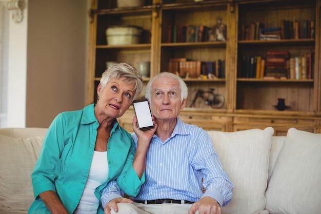 Couples aînés, utilisation, téléphone portable, dans, salle de séjour