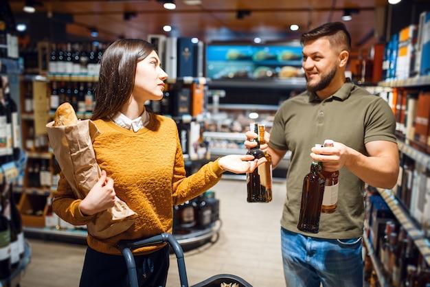 Couples attrayants choisissant l'alcool dans le supermarché d'épicerie