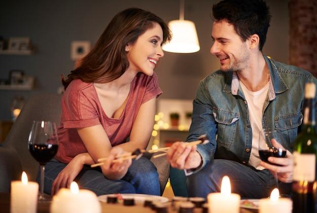 Couples attrayants essayant de la nourriture japonaise