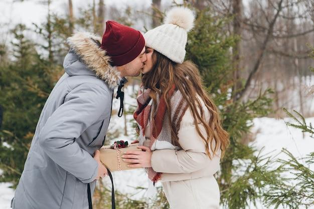 Couples câlins et bisous dans une forêt de conifères d'hiver, offrez-vous des boîtes avec des cadeaux