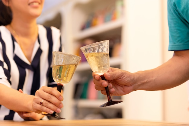 Les couples célèbrent avec du vin blanc à la maison.