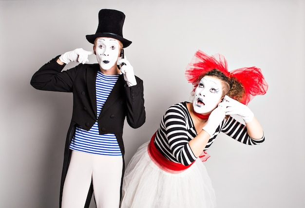 Couples drôles de mimes parlant par les téléphones. concept de poisson d'avril