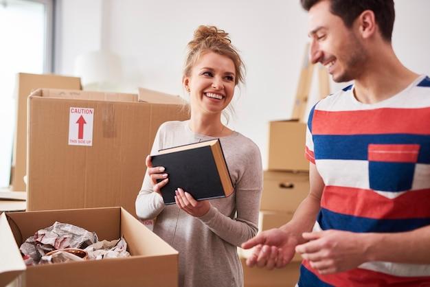 Couples emballant des livres dans les boîtes