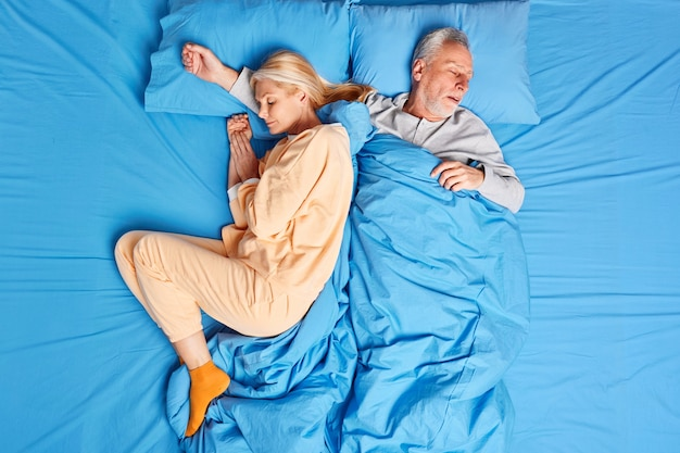 Les couples de famille mariés endormis dorment profondément la nuit et jouissent d'une atmosphère sereine vêtus de vêtements de nuit. une femme mûre et un homme font une sieste après une dure journée de travail se sentent à l'aise. concept de l'heure du coucher.