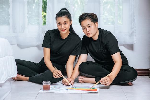 Les couples de femmes dessinent et peignent sur papier.