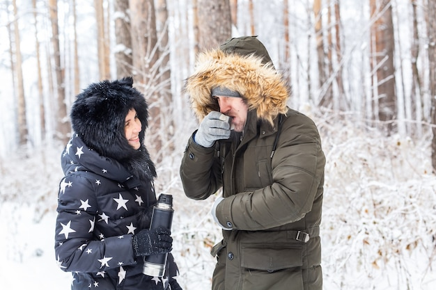 Couples heureux buvant du thé chaud dans la forêt d'hiver
