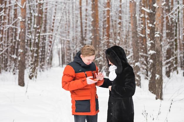 Couples heureux consultant un téléphone intelligent en hiver dans la rue