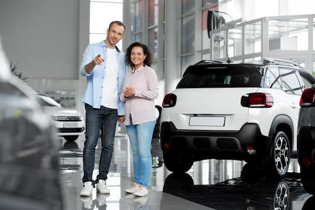 Couples heureux dans la concession de salle d'exposition de voiture
