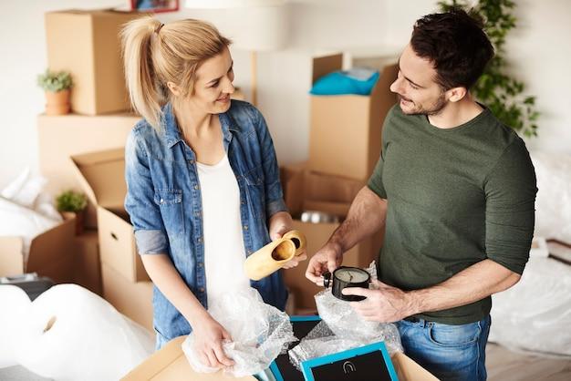 Couples heureux déballant leurs affaires des boîtes