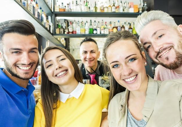 Couples heureux prenant selfie avec téléphone portable avec sympathique barman