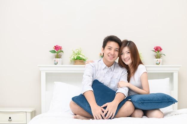 Les couples heureux sourient et jouent sur le lit à la maison, amour et concept romantique