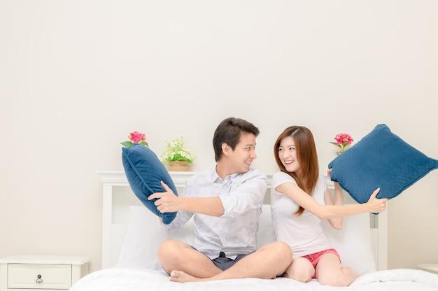 Les couples heureux sourient et jouent sur le lit à la maison