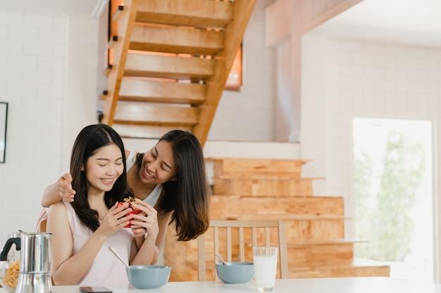 Couples lesbiennes asiatiques lesbiennes lgbtq donnant présent à la maison
