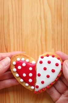 Couples mains tenant deux cookies en forme de demi-coeur attachent sur fond de bois