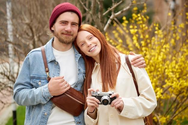 Couples mariés voyageurs en tenue décontractée à pied dans la forêt de printemps ou d'automne, avec caméra rétro