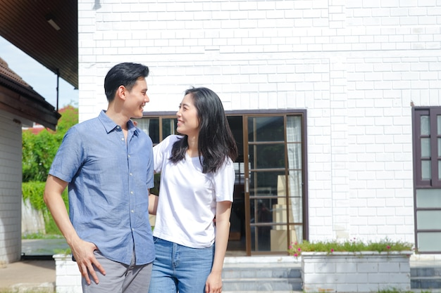 Les couples masculins et féminins asiatiques se tiennent, se serrent dans leurs bras et sourient joyeusement devant la nouvelle maison. le concept de commencer une vie conjugale afin de créer une famille heureuse. copie espace