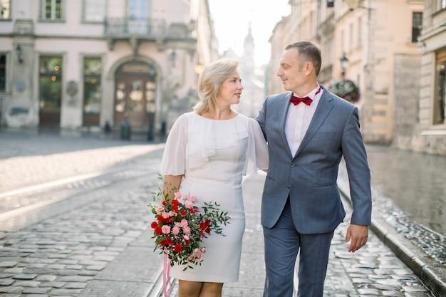 Couples mûrs dans des vêtements à la mode élégants, marchant dans la rue de la vieille ville européenne