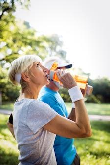 Couples mûrs ou seniors faisant du sport à l'extérieur, faisant du jogging dans un parc