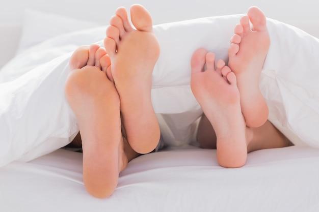 Couples pieds croisés sous la couette