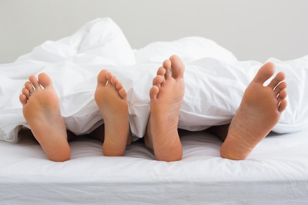 Couples pieds qui sortent de sous la couette