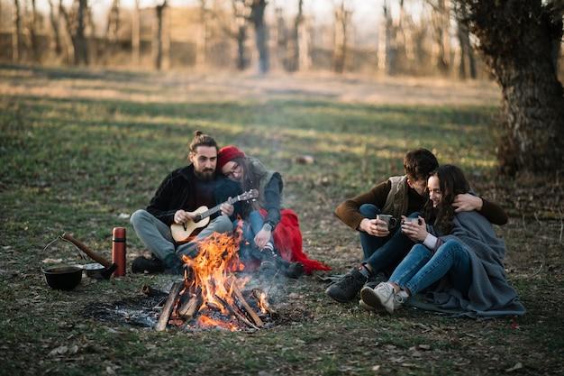 Couples pleins tir près d'un feu de camp