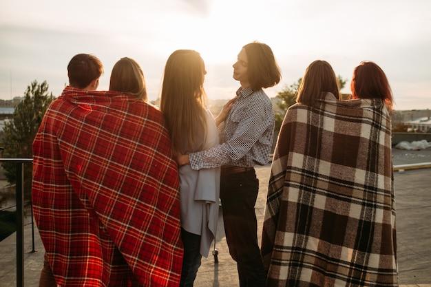 Les couples profitent du coucher de soleil sur le toit. romance, amour, beauté de la nature. émotion tranquille sentiments doux