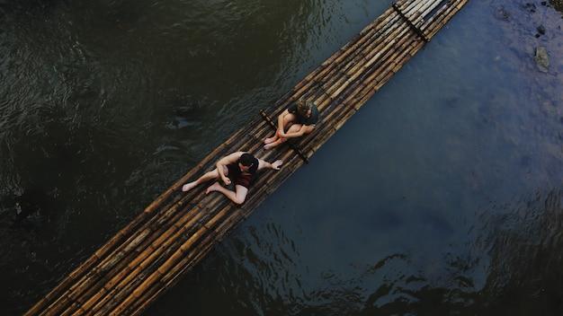 Couples avec radeau de bambou en thaïlande pendant l'été