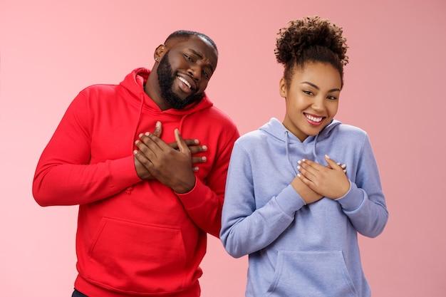 Les couples reçoivent des compliments qui vont bien ensemble. portrait charmant sympathique aimant petite amie afro-américaine copain presse paumes coeur touché heureux souriant largement reconnaissant mots émouvants