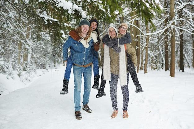 Couples s'amusant dans la forêt d'hiver