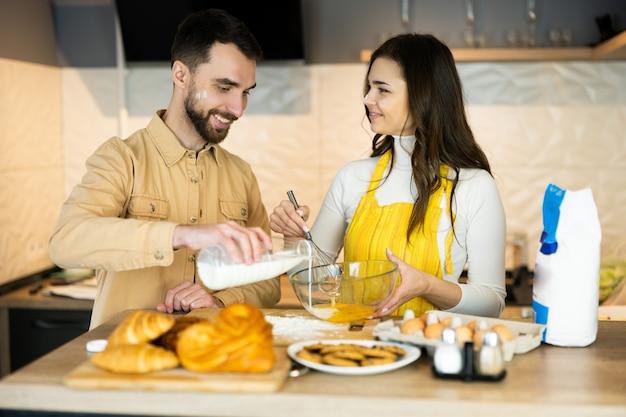 Les couples s'amusent en cuisinant et semblent heureux d'être ensemble dans la cuisine.