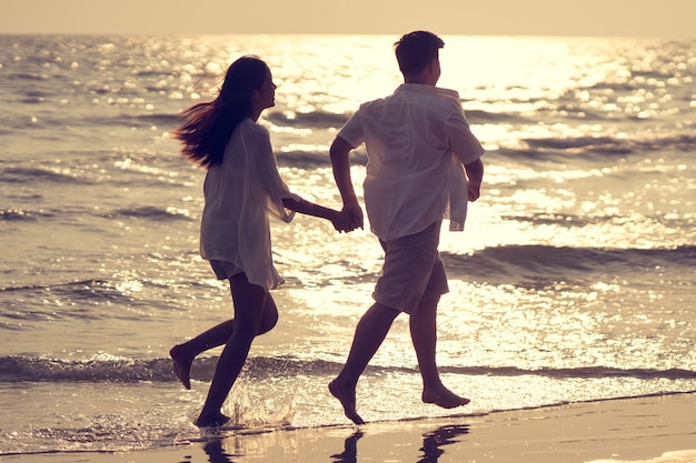 Couples tenant la main beach se défouler joyeusement