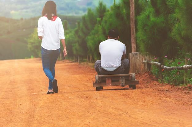 Couples de voyageurs marchant et assis sur la voiture à roues en bois.