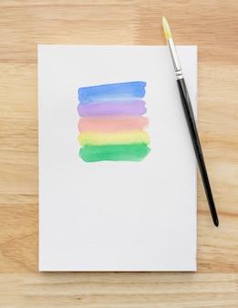 Coups de pinceau aquarelle coloré sur feuille de papier blanc avec fond en bois. fermer.