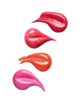 Coups de pinceau brillant à lèvres dans différentes nuances isolés sur blanc