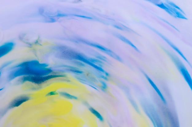 Coups de pinceau de couleur jaune et bleue sur une toile blanche