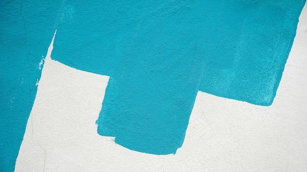 Coups de pinceau de peinture bleue sur un mur de béton blanc - fond