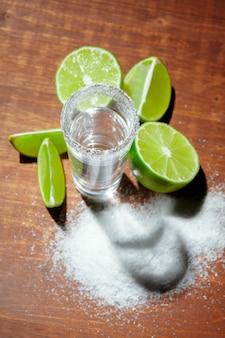 Coups de tequila en argent avec des tranches de citron vert et du sel sur une planche en bois