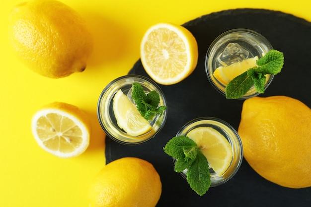 Coups avec tranche de citron et menthe sur un plateau sur une surface jaune