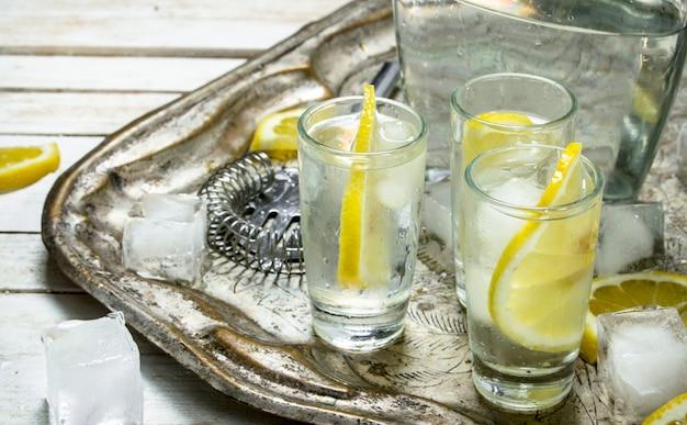 Coups de vodka avec du citron et de la glace sur une table en bois blanche.