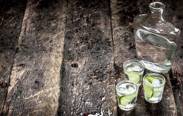 Coups de vodka avec de la glace et de la chaux fraîche sur une table en bois.