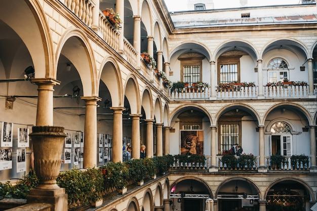 Cour italienne dans le vieux centre-ville de lviv avec les touristes qui la regardent.