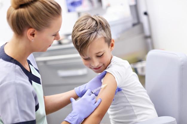 Courageux petit garçon recevant une injection ou un vaccin avec un sourire