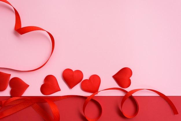 Courbes de ruban rouge saint-valentin en forme de coeur sur fond rose. fond festif pour mariage et cartes de voeux, maquette, espace de copie.